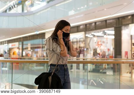 Young Woman In A Reusable Protective Mask In A Shopping Center. Respiratory Protection During The Co