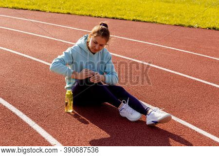 Sports Injuries, A Young Female Athlete Kneads Her Knee, Sprains Or Muscles. Runner In A Blue Hoodie
