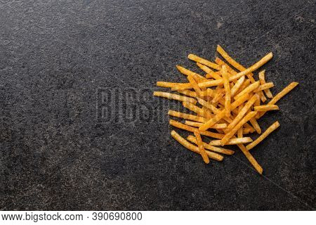 French fries. Fried mini potato sticks on black table. Top view.