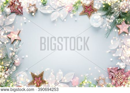 Christmas  frame with festive decorations,fir branches, silver leaves, pine cones, baubles on pastel background. Flat lay. Top view, copy space.