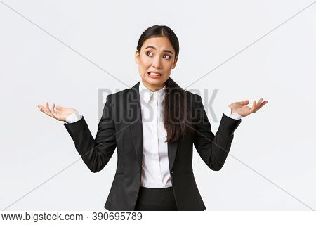 Troubled Young Female Office Assistant, Saleswoman In Black Suit Shrugging And Looking Away Worried,