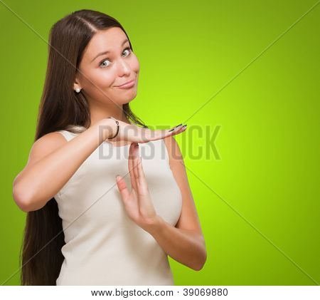 Portrait Of Young Woman Showing Time Out Signal against a green background