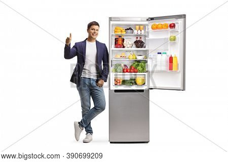Full length portrait of a young man leaning on a full fridge and showing thumbs up  isolated on white background