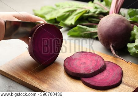 Woman Cutting Fresh Red Beet At Table, Closeup
