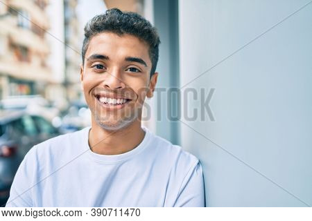 Young latin man smiling happy leaning on the wall at the city.