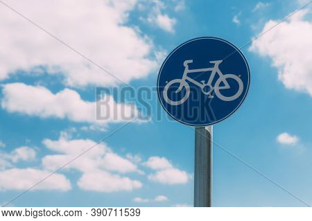 Close-up View Of Round Blue And White Bicycle Lane Sign Against A Blue Sky With Clouds. Outdoor Sign