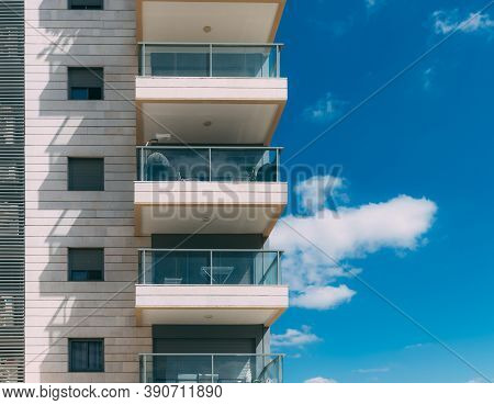 Balconies And Blue Sky With Clouds. Part Of A Residential Building In Israel. Modern Apartment Build