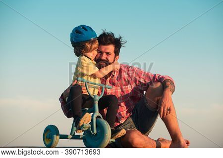 Lovely Father Teaching Son Riding Bike. Happy Dad Helping Excited Son To Ride A Bicycle. Young Smili
