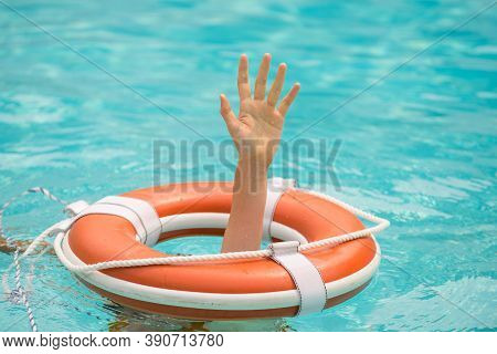 Lifebuoy With Hands In The Water. Life Buoy And Helping To Survive. Support Survival Or Save