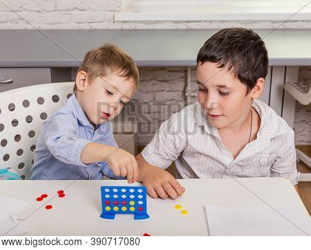 The Game Who Will Quickly Collect 4 Chips In A Row. Portrait Of Two Cheerful Children Are Smiling An