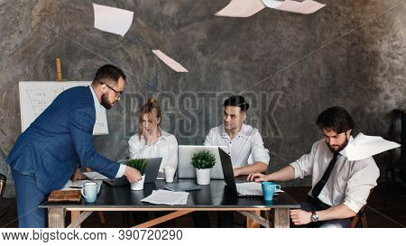 Angry Boss Reprimanding Employee For Bad Work Result Sitting At Conference Table, Male Ceo Scolding