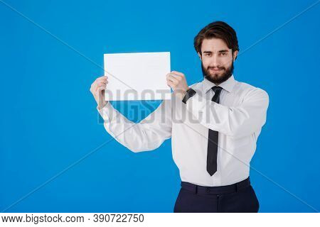 Male Businessman In A Shirt And Tie On A Blue Background. A Young Bearded Guy Is Holding A Piece Of
