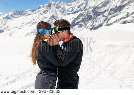 A Couple Embracing Outside, Wear In Ski Goggles, On Beautiful Winter Mountain Background. Winter Tra