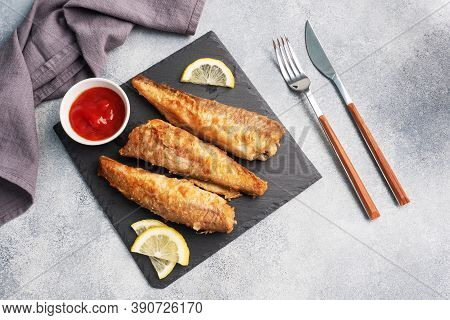 Fried Fish Hake Pollock With Tomato Sauce And Slices Of Fresh Lemon. Concept Eating Fatty Fast Food.