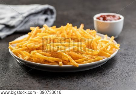 French fries on plate. Fried mini potato sticks on black table.