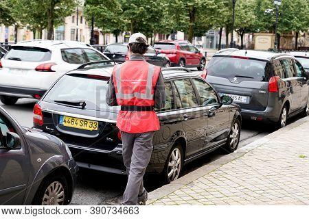 Bordeaux , Aquitaine / France - 16 10 2020 : Traffic Warden Civil Enforcement Officer Issuing Parkin