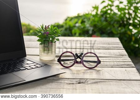 Outdoor Office Desk, Computer Laptop In The Garden, Glasses On The Table, Green Nature Background, Q