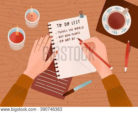 Desk With Candles, A Cup Of Coffee On It And Womans Hands Writing Plan In Notebook. Person Filling T