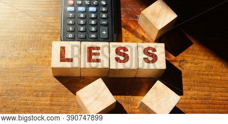 Less Word On Wooden Alphabet Blocks And Calculator. Spend Less, Save More Business Concept