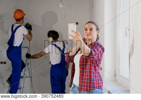 Young Woman Smiles And Takes A Selfie On The Phone. In The Background, Handymen In Overalls Are Dril