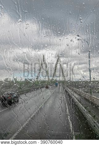 View Of A Road Over The Cable-stayed Bridge In Rainy Weather Through The Glass Flooded With Water