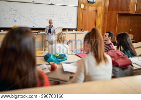 A female professor giving a lecture to students in the university amphitheater. Smart young people study at the college. Education, college, university, learning and people concept