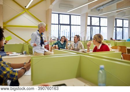 A relaxed female professor talking to students about the lesson in the university classroom. Smart people study at the college. Education, college, university, learning and multiethnic people concept