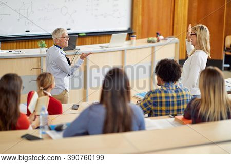 A female professor questioning students at the lecture in the university amphitheater. Smart young people study at the college. Education, college, university, learning and multiethnic people concept