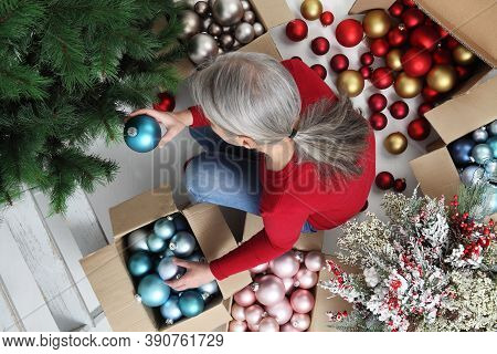 Woman Prepare Christmas Tree With Cardboard Boxes Full Of Christmas Balls And Decorations, Preparati