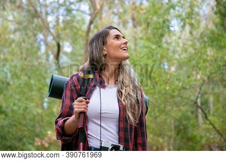 Beautiful Young Woman Hiking In Mountains With Backpack. Excited Female Traveler Looking Around And