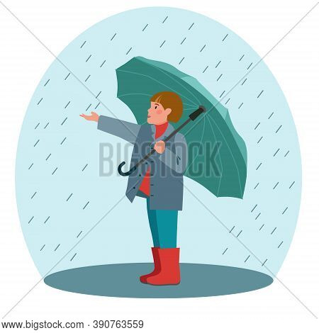 Boy With An Open Umbrella Standing Under The Raindrops. Schoolboy With An Umbrella In The Rain. Rain