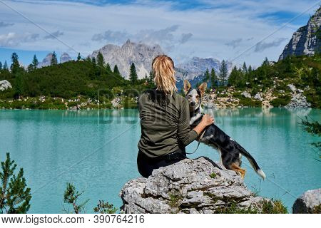 a woman with a dog is resting on the shore of a mountain lake. vanlife