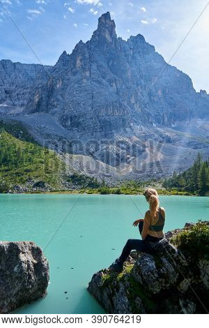 a woman  is resting on the shore of a mountain lake. vanlife