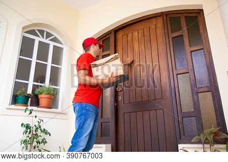 Angled View Of Courier Knocking At Door And Holding Paper Bag And Clipboard. Professional Deliveryma