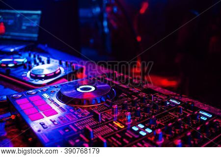 Dj Console For Mixing Music With Blurry People Dancing At A Nightclub Party