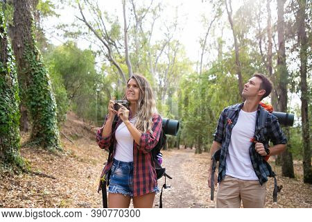 Beautiful Woman Taking Photo Of Landscape With Camera And Traveling With Pensive Man. Caucasian Hike