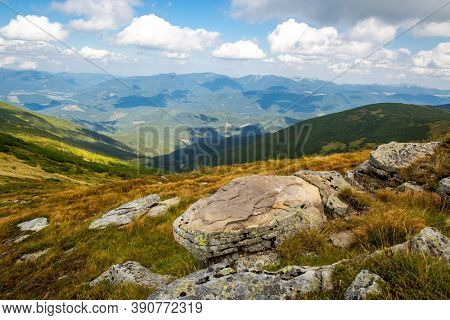 Landscape with old stones in dry grass on meadow in Carpathian mountains, Ukraine