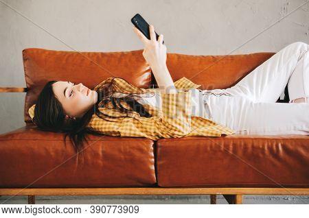 Young Calm Caucasian Stylish Woman Using Smartphone, Relaxing Lying On Comfortable Sofa In Modern Li