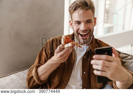 Photo of cheerful handsome young man sitting on sofa indoors at home and eating pizza while talking by videocall by mobile phone