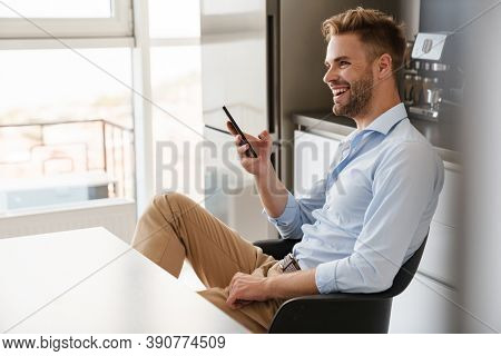 Image of cheerful optimistic young businessman sitting indoors at home at the kitchen and using mobile phone