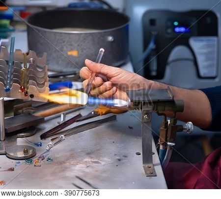 Hand Holding Glass Stick In Flame Of High-temperature Torch. Murano Glass Lampworking (flameworking)