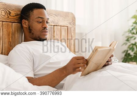 Black Man Enjoying Reading Book In The Morning Lying In Comfortable Bed At Home. Bookworm Guy Reads