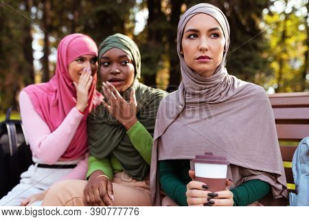 Adult Bullying. Muslim Ladies Whispering Behind Back Of Female Friend Sitting On Bench In Park Outdo