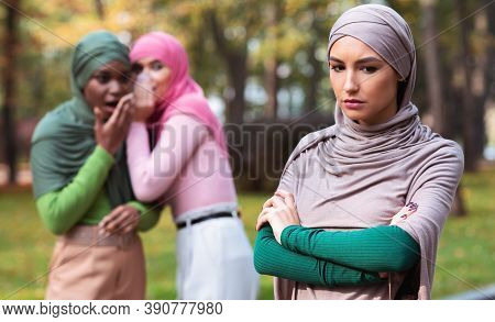Bullying. Fake Friends Talking About Unhappy Muslim Woman Standing Alone In Park Outdoor. Female Fri