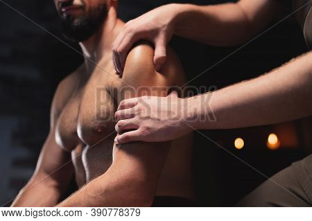 Male Shoulder And Deltoid Muscle Massage To Athlete Muscular Man In Dark Room Of Spa Salon While Sit