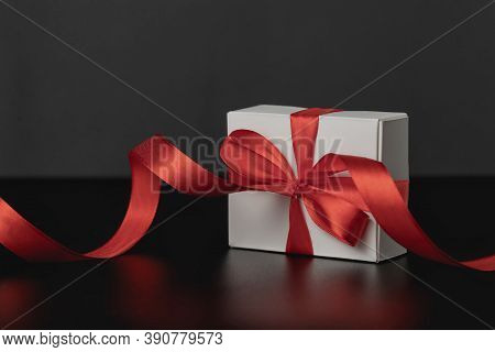 Close-up View Of White Gift Box With Elegant Red Ribbon In Luxury Bow On Dark Background And Reflect