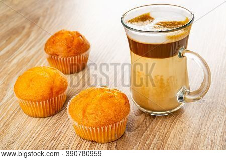Three Orange Muffins, Transparent Glass Cup With Latte-macchiato On Wooden Table