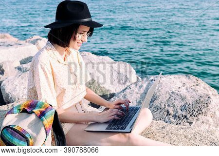 Young Traveler Woman Working With Computer And Backpack By The Sea, Concept Of Digital Nomad And Blo