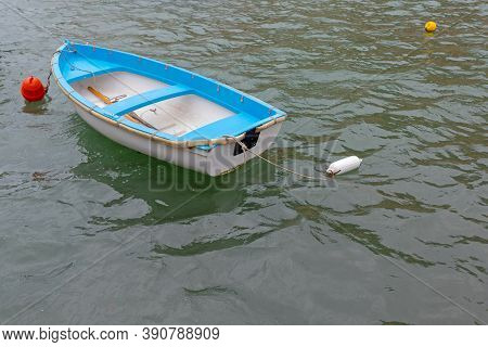 Small Plastic Dinghy Boat Moored At Sea