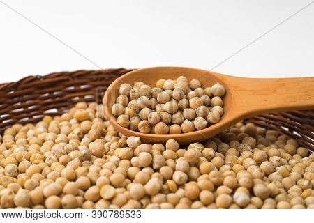 Chickpeas In A Wooden Spoon On A Wicker Plate. Raw Chickpea.